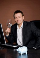 Businessman holding a glass, looking at the camera with piggy bank on focus