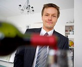 Blurrred wine bottle and glass with a businessman in the background (thumbnail)