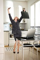 Businesswoman dancing with joy in the kitchen
