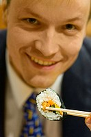 Businessman holding a sushi roll with chopsticks