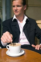 Businessman sitting in a cafe having coffee (thumbnail)