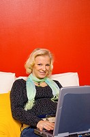 Woman smiling at the camera while using laptop