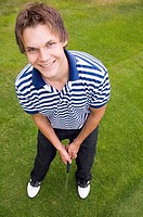 Man smiling at the camera while playing golf