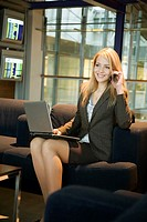 Businesswoman using laptop while talking on mobile (thumbnail)