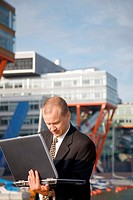 Businessman using laptop outdoors (thumbnail)