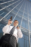 Businessman smiling while text messaging on the mobile phone
