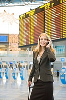 Woman talking on the mobile with arrival departure board in the background (thumbnail)
