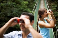 Man and Woman on Bridge Looking Through Binoculars