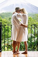 Mature Couple in Bathrobes Embracing Outdoors