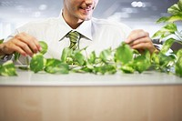 Businessman Tending to Plant in Office