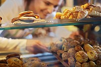 Deli Owner Placing Tray of Pastries in Display Case