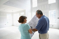 Senior Hispanic couple looking at blueprints in new house