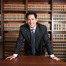 Mixed Race male lawyer leaning on desk