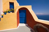 Yellow house, cascading flowerpots, blue door and sea view. Santorini. Greece