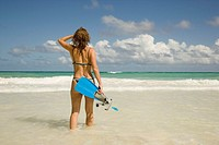Woman carrying snorkeling gear at beach