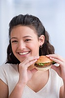 Hispanic girl eating hamburger