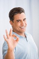 Hispanic man making okay hand gesture