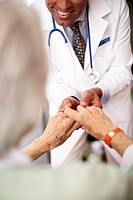 Senior Woman Holding Doctor's Hands (thumbnail)