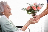 Senior Woman Receiving Gift of Flowers