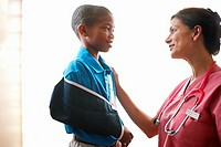 Nurse Talking to Young Boy with Arm in Sling