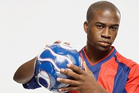 African American male soccer player holding ball