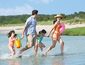 Hispanic family walking through water at beach