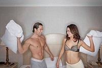 Couple in underwear having pillow fight