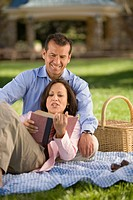 Hispanic couple reading on picnic blanket