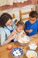 Hispanic grandmother cooking with grandchildren