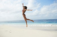 South American woman jumping on beach (thumbnail)