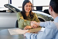 Woman shaking hands with car salesman