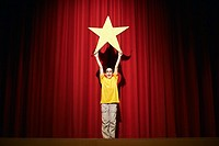 Boy on Stage Holding a Star