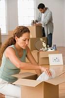 Hispanic couple packing moving boxes
