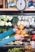 Woman weighing fruit at grocery store