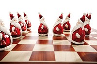 Santa Claus figurines standing on a chessboard