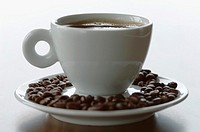 Cup of coffee with roasted beans, close-up