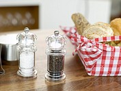 Salt and pepper with bread basket on table