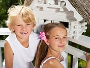 Girl and boy sitting in front of birdhouse, portrait