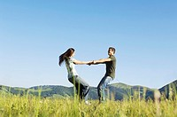 Young couple dancing in mountain field side view ground view