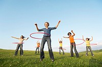 Group of friends using hula hoops in mountain field low angle view