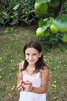 Girl 10_12 holding apple in garden
