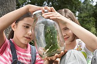 Two girls 7_9 examining stick insects in jar outdoors