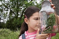 Girl 7_9 examining jar of stick insects outdoors