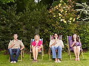 Group of young people sitting in row on deckchairs in garden eating ice creams