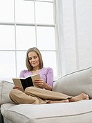 Mid adult woman reading book on sofa (thumbnail)