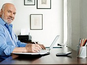 Middle_aged man sitting at desk using laptop and writing in notepad