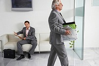 Business man carrying box past a man reading newspaper in office hallway (thumbnail)
