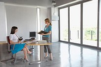 Two women talking at desk in empty office building