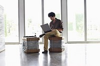 Young man using laptop sitting on packages in empty office