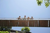 Parents and two sons 7-12 on bridge looking down (thumbnail)